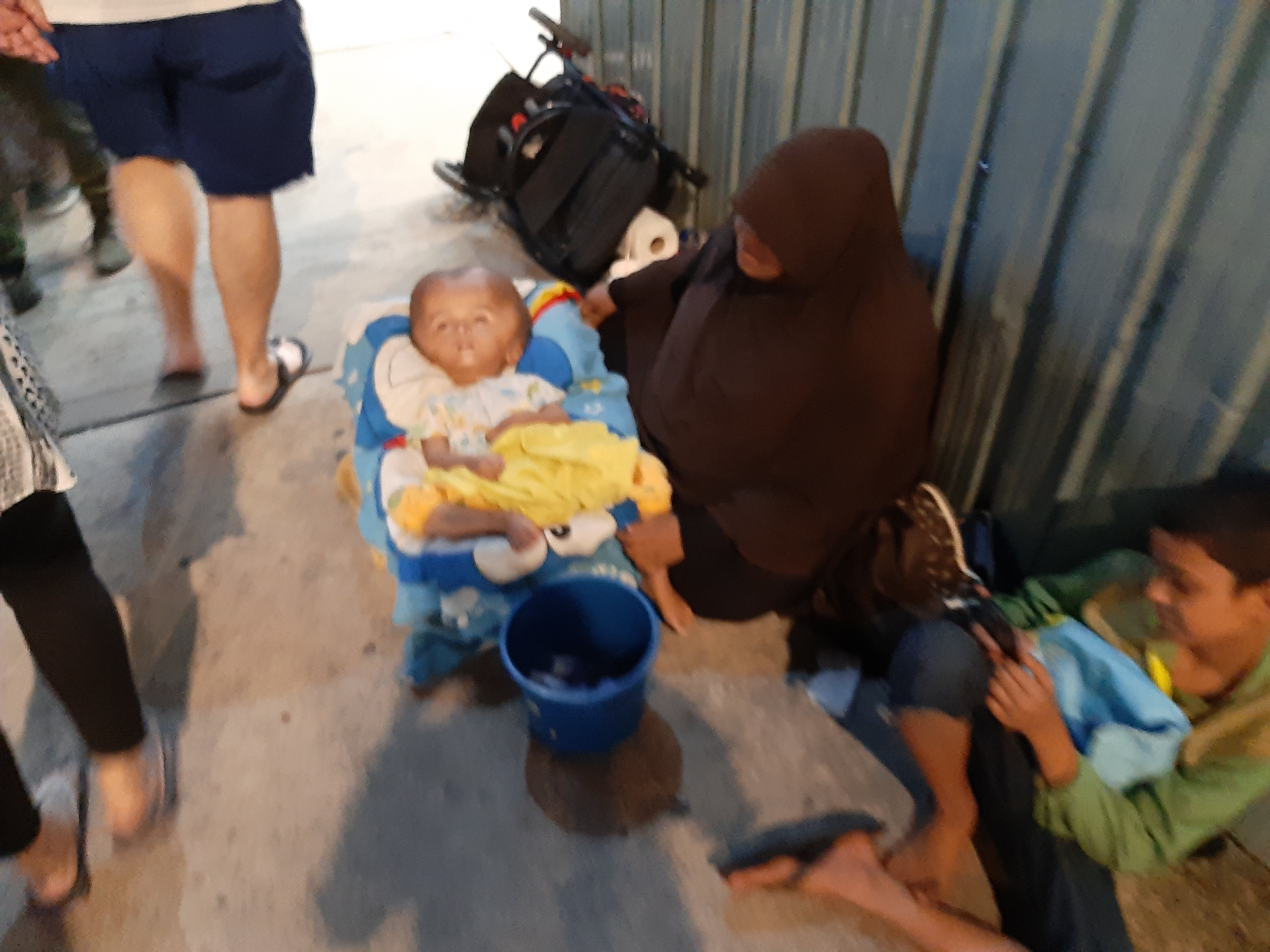 Sick child with hydrocephalus, begging mother.