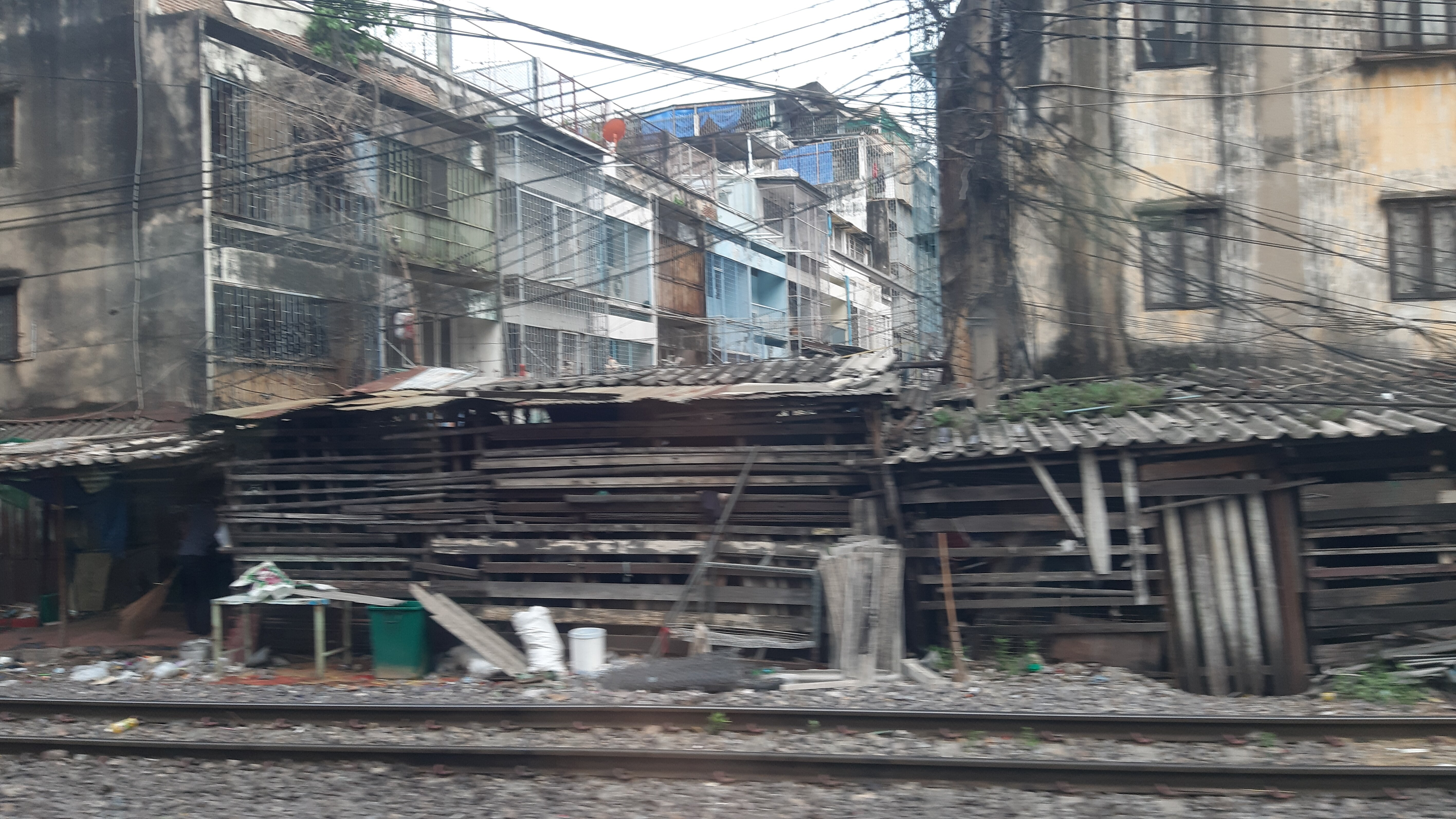 Shacks and apartments by the side of the road. A man can be seen sweeping at the left of the frame.